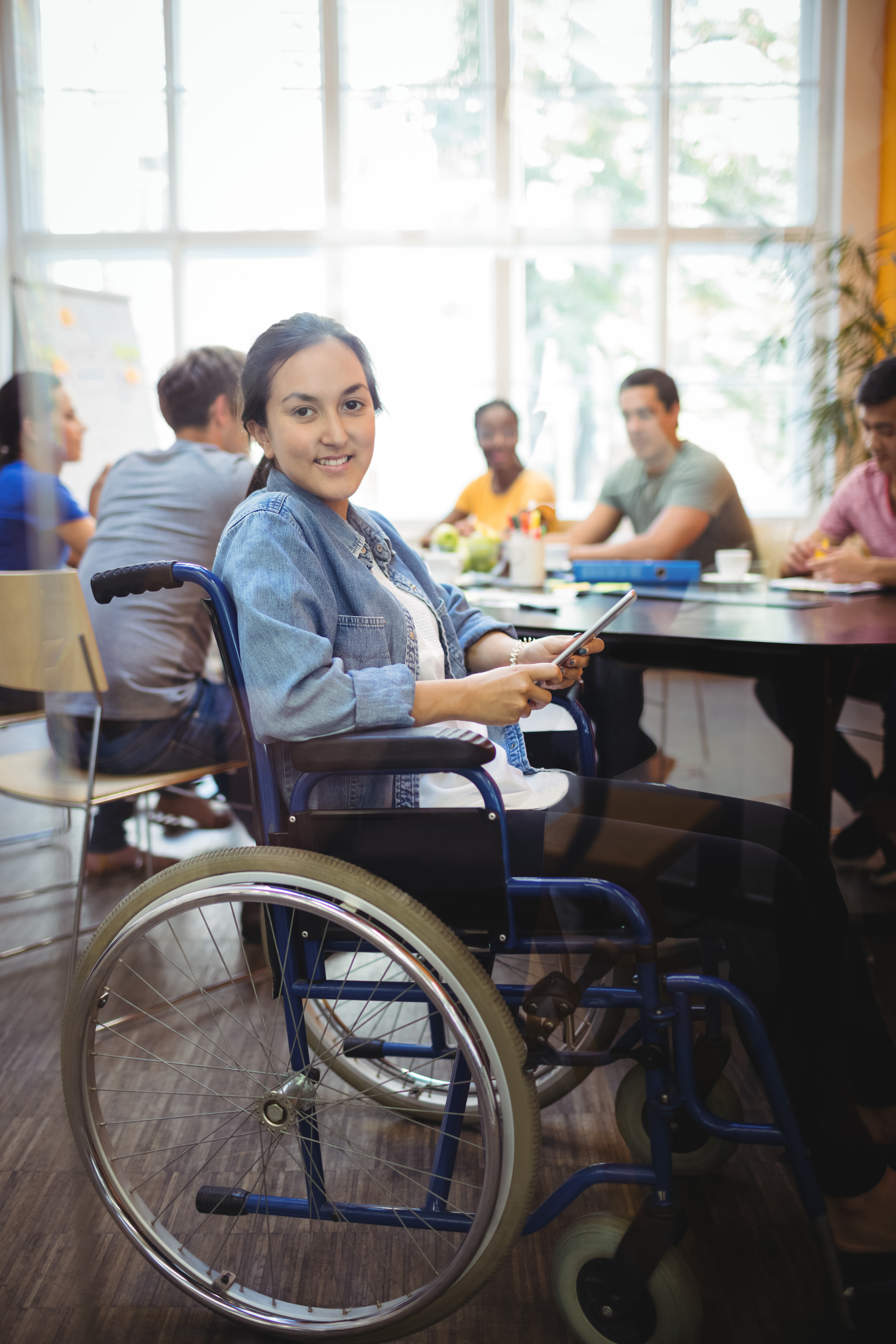 Portrait of handicapped business executive using digital tablet in office